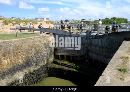Bude, Cornwall, UK. Holidaymakers enjoy the hot weather walking along the Bude canal and crossing the Sea lock - Stock Image