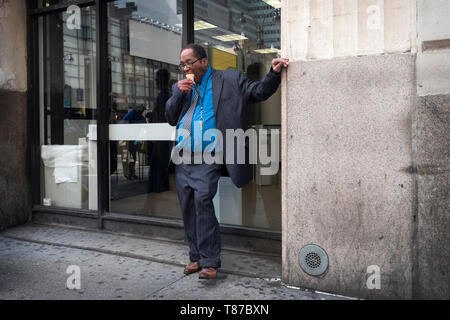A man eating an ice cream cone outside of an office building on Eighth avenue in Manhattan, New York City. - Stock Image