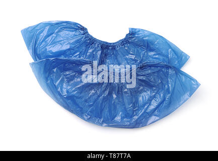Top view of two disposable medical blue plastic shoe covers isolated on white - Stock Image