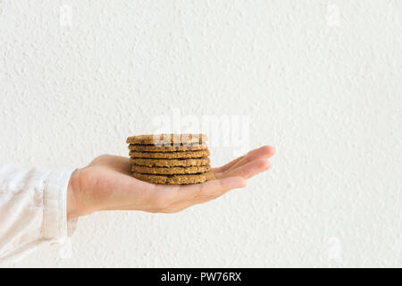 Young caucasian woman holds in stretched hand stack of chocolate chip cookies with oats bran nuts on white wall background. Holiday baking healthy pas - Stock Image