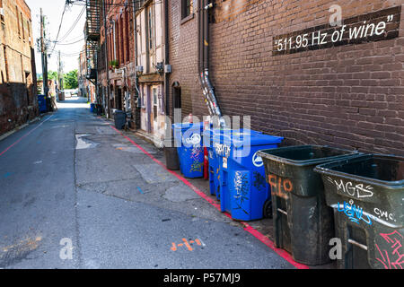 ASHEVILLE, NC, USA-24 JUNE 18: An urban alley with trash cans, and a cryptic sign stating '511.95 Hz of wine.' - Stock Image
