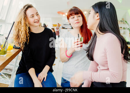 Three young girlfriends chatting while drinking coktail on free time - Stock Image