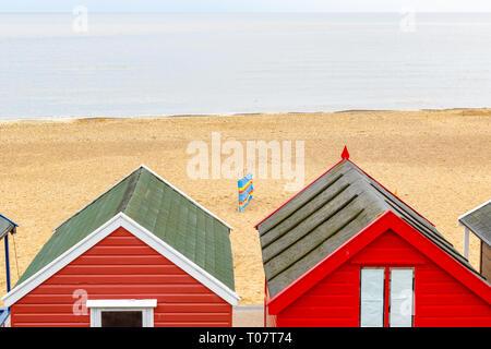 A beach windbreak seen through beach huts on Southwold beach in the UK - Stock Image