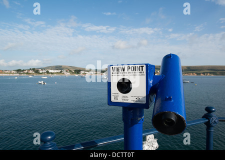 View point blue telescope situated on Swanage pier with an observation  view across the bay - Stock Image