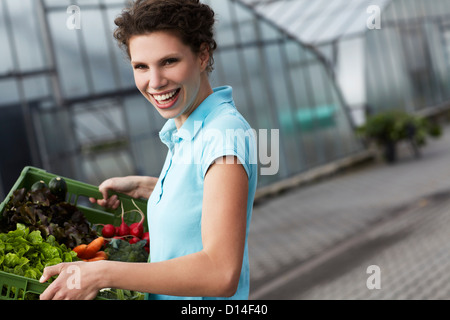 portrait of young woman with basket full of vegetables - Stock Image
