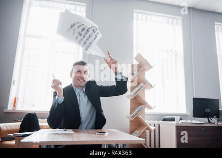 A handsome man sitting in the office and throwing papers on the air - Stock Image