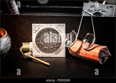 Coin Collector's Desk with rolled coins, magnifiers, Ceylon 2500 years of Buddhism Coin - Stock Image