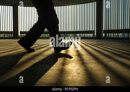 Backlighted low section of a man walking in the shadow of a car park. - Stock Image