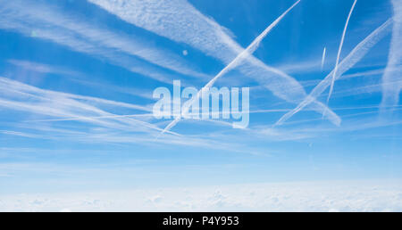 Multiple contrails cross paths through the sky above a layer of cloud over Germany. - Stock Image