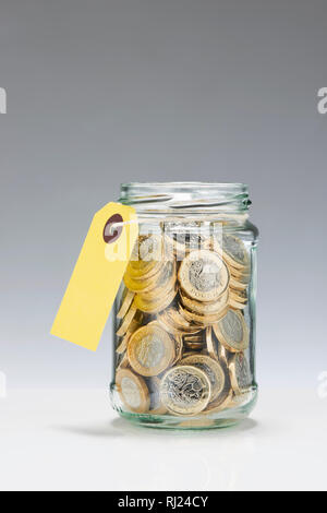 Glass Savings Jar with One Pound Coins - Stock Image