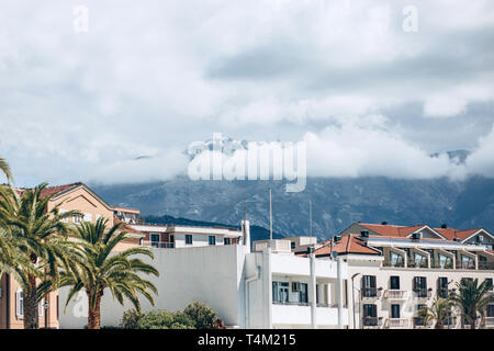 Beautiful view of the architecture of Tivat in Montenegro against the backdrop of mountains with clouds. - Stock Image