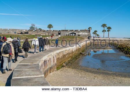 A senior tour group approaches the Castillo de San Marcos, a Spanish fortification at St. Augustine, Florida USA - Stock Image