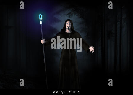 Black wizard in the dark forrest with lighting diamond on the stick. - Stock Image