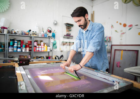 Young male printer using squeegee in printing press studio - Stock Image