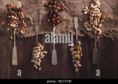 Different types of nuts on old spoons and compositions made of old wood and material - Stock Image