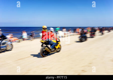 Motorcyclists ride on the beach sunbathing among people - Stock Image