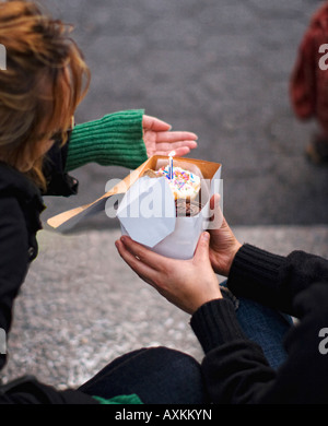 NY street scene of two young people having a small celebration - Stock Image