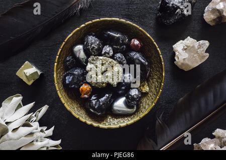 Crow Feathers and Mixed Stones with White Sage on Black Wood - Stock Image
