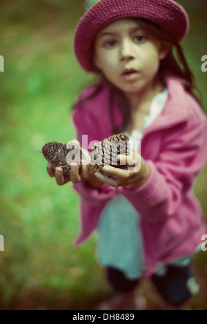 Girl holding pine cones - Stock Image