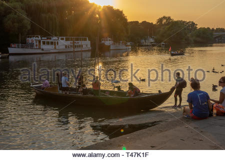 People boarding large rowing boat at sunset in Richmond Upon Thames - Stock Image