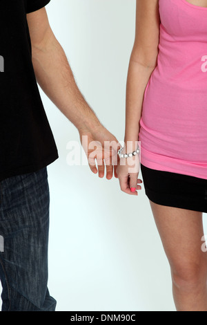 Young adult male touching the hand of a young female wearing a short skirt and a tight pink top. Isolated on white - Stock Image
