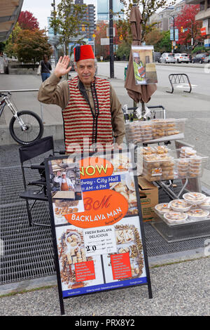 Elderly Syrian refugee man selling homemade baklava in Vancouver, BC, Canada - Stock Image