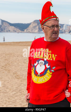 Benidorm, Costa Blanca, Spain, 25th December 2018. British tourists dress for the occasion on Christmas Day in this favourite getaway destination for Brits escaping the cold weather at home. Temperatures will be in the mid to high 20's Celsius today in this mediterranean hotspot. Middle aged man wearin bright red christmas jumper and hat. - Stock Image