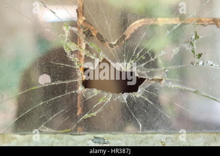 Smashed window pane with a hole in the middle - Stock Image