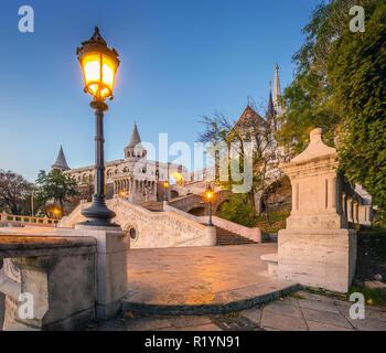Budapest, Hungary - Sunrise at the entrance of Fisherman's Bastion (halaszbastya) with street-lamp, Matthias Church, autumn foliage and clear blue sky - Stock Image