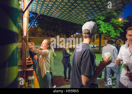 Group of customers at food truck at night - Stock Image