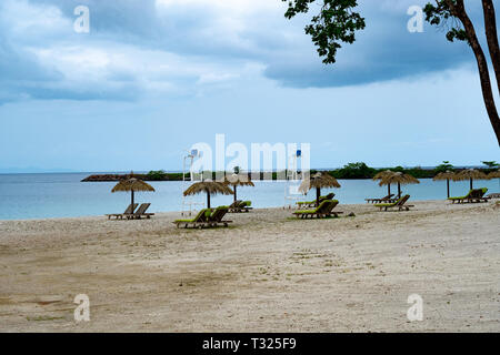 A view of the sea shore of Bioko Island, Equatorial Guinea, with a beach and sun loungers in the foreground - Stock Image