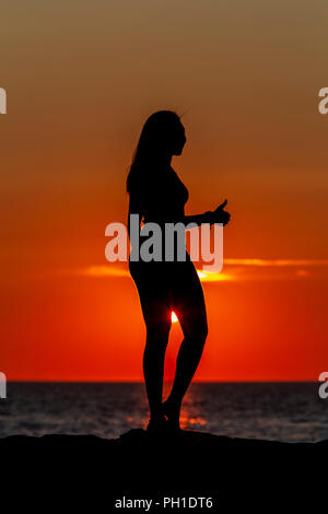 A woman gives a 'thumbs up' while silhouetted at sunset on the jetty at Menemsha Beach in Chilmark, Massachusetts on Martha's Vineyard. - Stock Image