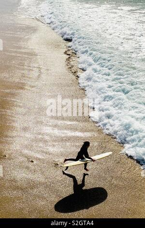 A young male surfer runs into the water. Manhattan Beach, California USA. - Stock Image