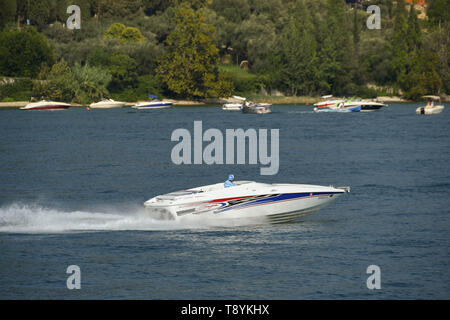 LAKE GARDA, ITALY - SEPTEMBER 2018: Sleek motor boat at speed across the blue water of Lake Garda. - Stock Image