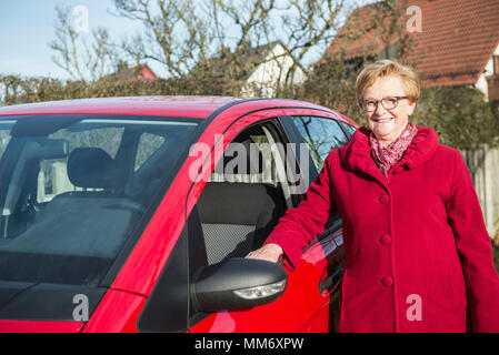 Portrait of old woman standing beside car - Stock Image