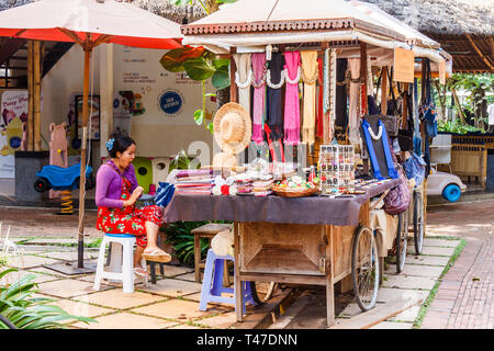 Siem Reap, Cambodia - 10th January 2018: Vendor selling souvenirs at the King Road craft market. All sorts of handicrafts are sold. - Stock Image