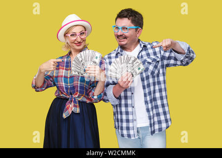 Couple of wealthy friends, adult man and woman in casual checkered shirt standing together holding fan of dollars and pointing fingers, toothy smile, - Stock Image