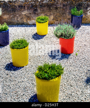 Colorful vases on a gravel patio. - Stock Image