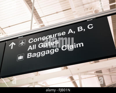 Airport concourse, gates, and baggage claim sign - Stock Image