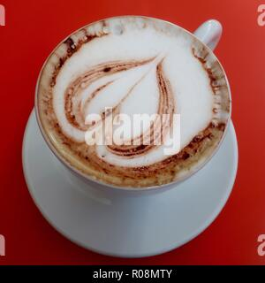 Barcelona, Spain, October 2018. Cappuccino coffee in a white cup and saucer on a red table. - Stock Image