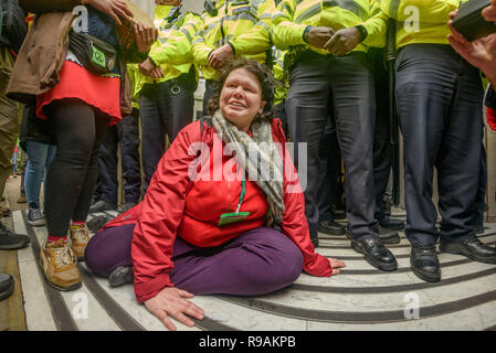 London, UK. 21st December 2018.A woman from Extinction Rebellionsuperglues herslf to the pavement at the entrance to BBC's Wogan House calling it to stop ignoring the climate emergency & mass extinctions taking place and promoting destructive high-carbon living through programmes such as Top Gear and those on fashion, travel, makeovers etc. The protest, organised by the Climate Media Coalition (CMC) and its director Donnachadh McCarthy brought mannequins wrapped in white cloth to the BBC representing the bodies of a Greek village killed by fire. Peter Marshall/Alamy Live News - Stock Image