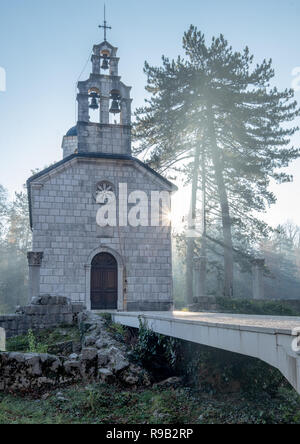 Christian Orthodox church on a clear brisk fall morning, with fog and frost, with ray of sun beaming towards the church and tree, and a sun burst - Stock Image