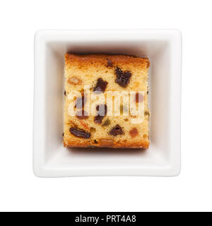 Slice of fruit cake in a square bowl isolated on white background - Stock Image