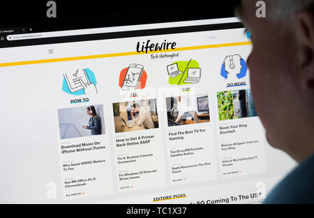 Man sitting at a computer monitor browsing through the Internet looking at the Lifewire website on the World Wide Web using an Internet Browser. - Stock Image