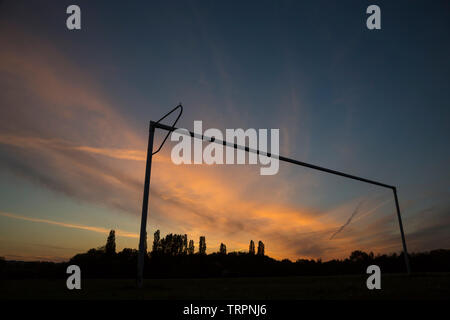 Landscape capture of a beautiful, spectacular, evening sunset sky as seen through the silhouette of a football goals post in a British, public park. - Stock Image