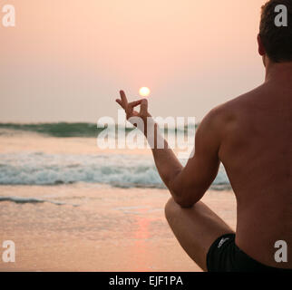 A man meditating on a beach at sunset - Stock Image