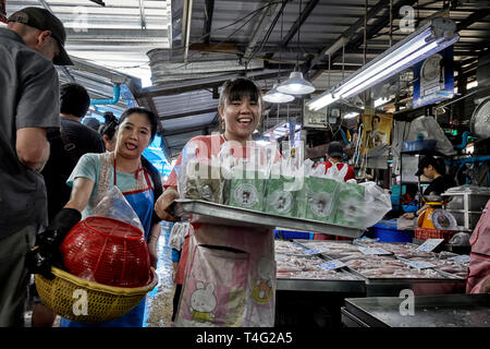Happy and smiling Thai woman carrying a tray of food cartons in a Thailand Market, Southeast Asia - Stock Image