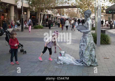 A little girl putting money in a tin for a street performer in Perth's Murray street mall. Western Australia. - Stock Image