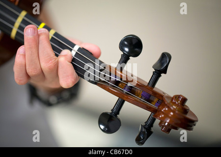 The hand of a child playing a violin. - Stock Image
