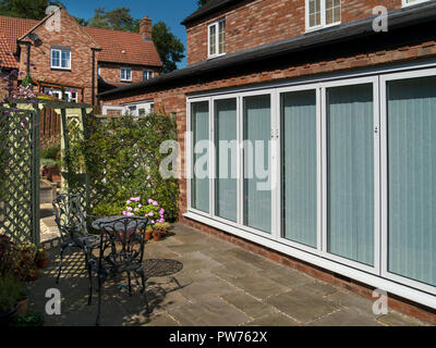 Exterior view of modern garden room with large white aluminium framed six double glazed panel bi-fold patio doors - Stock Image